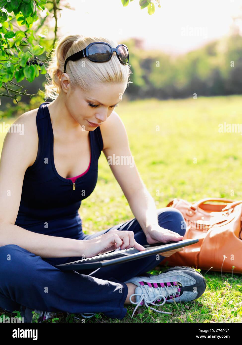 Una mujer en ropa deportiva sentados en el césped utilizando una tableta digital Imagen De Stock