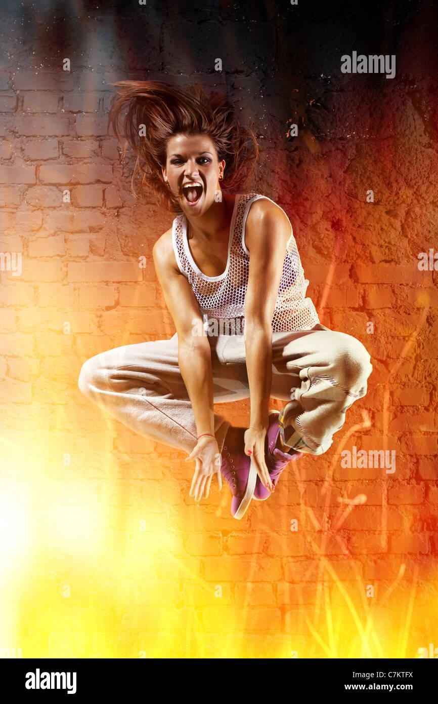 Mujer joven bailarín saltando. Con efecto de fuego. Imagen De Stock