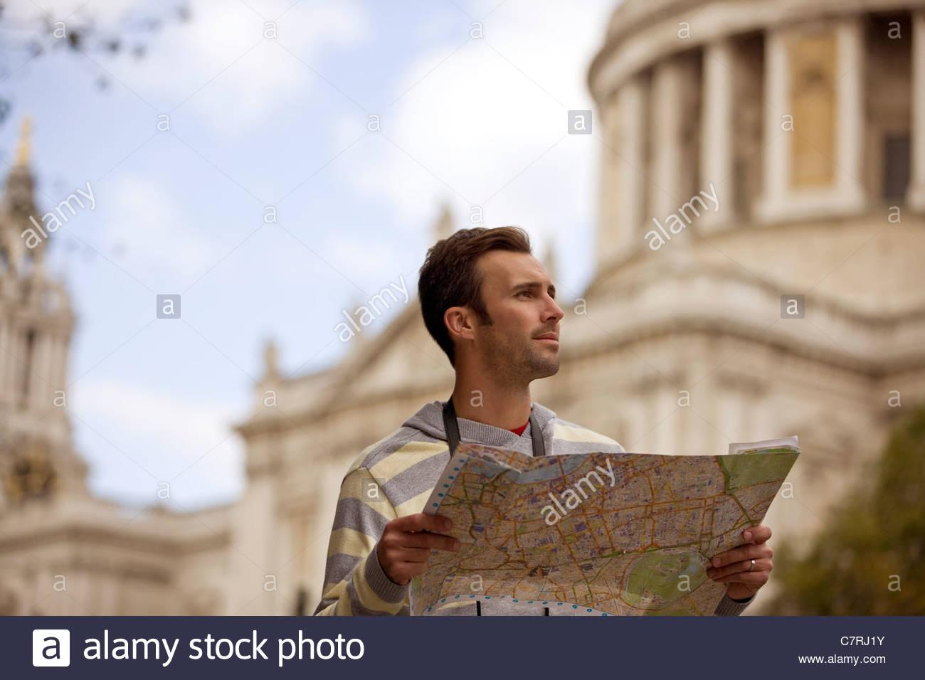 Un hombre adulto medio de pie en frente de la catedral de St Paul, mirando un mapa Imagen De Stock