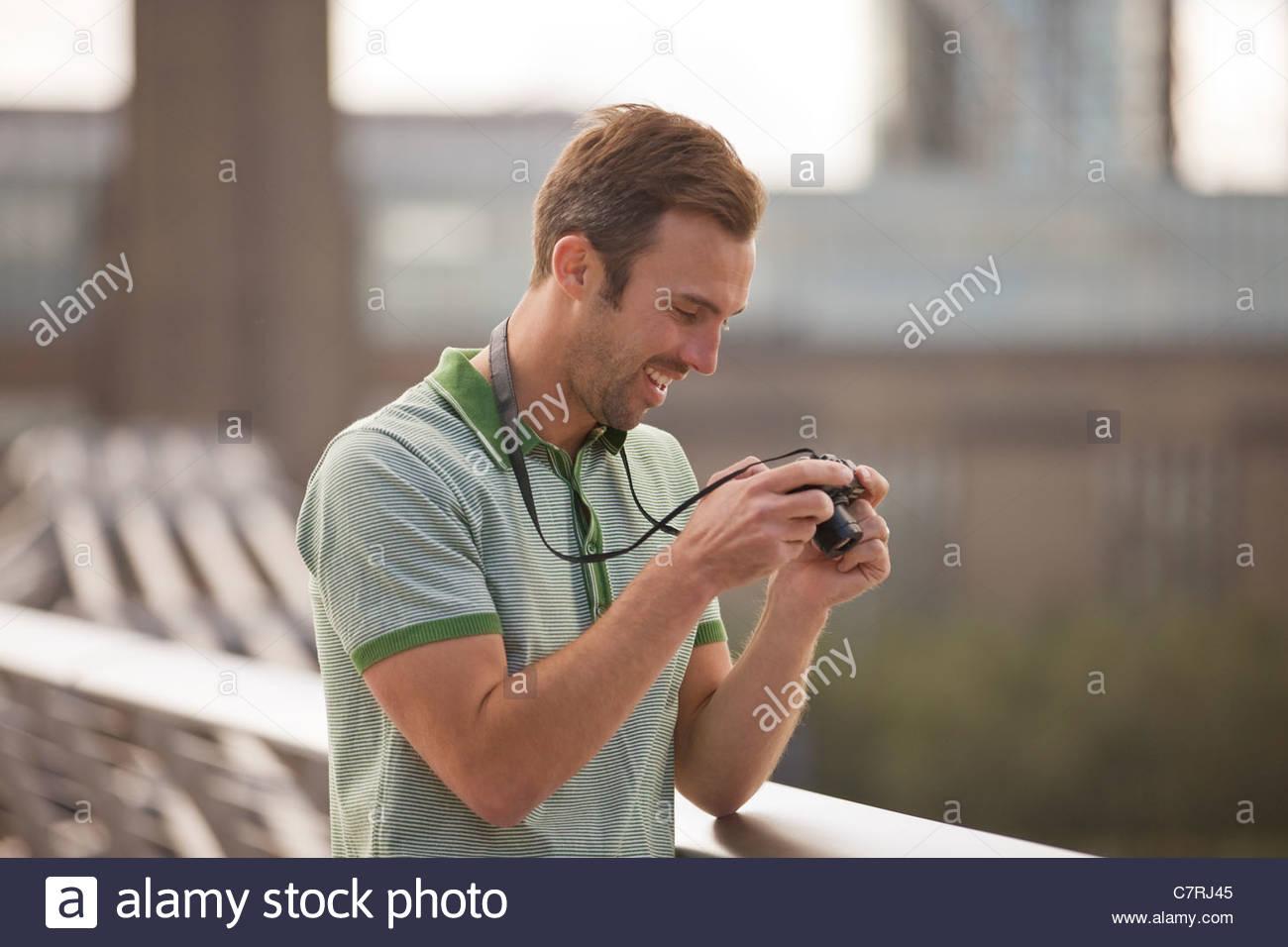 A mediados de hombre adulto mirando sus fotografías de su cámara Imagen De Stock
