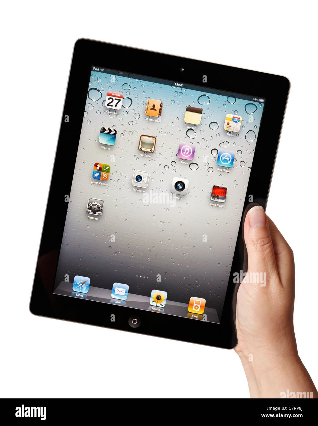 Mano sosteniendo el iPad que muestra la pantalla del menú de aplicaciones Imagen De Stock