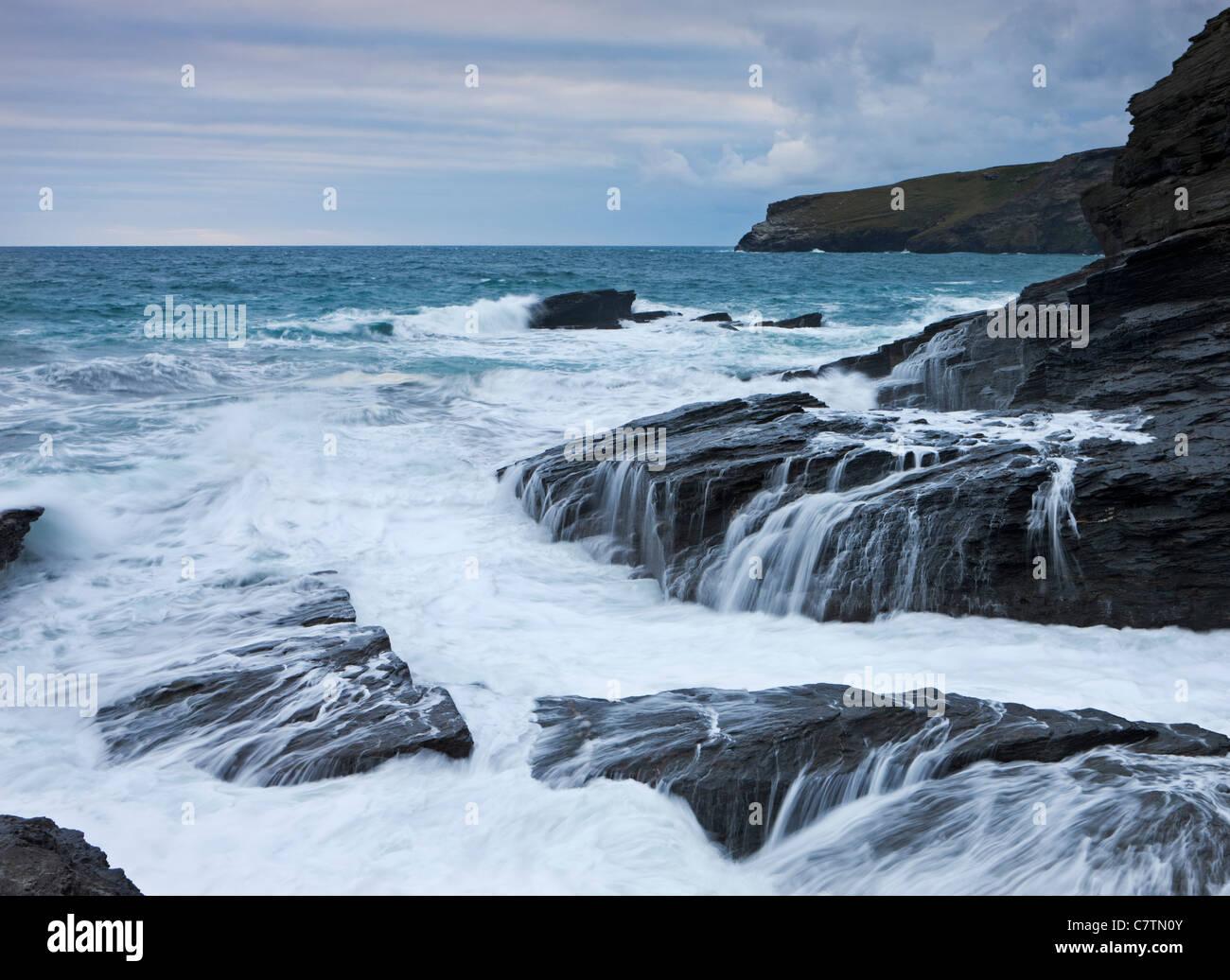 Feroz bloqueo olas del Atlántico a lo largo de los acantilados de pizarra oscura Trebarwith Strand, Cornwall, Imagen De Stock