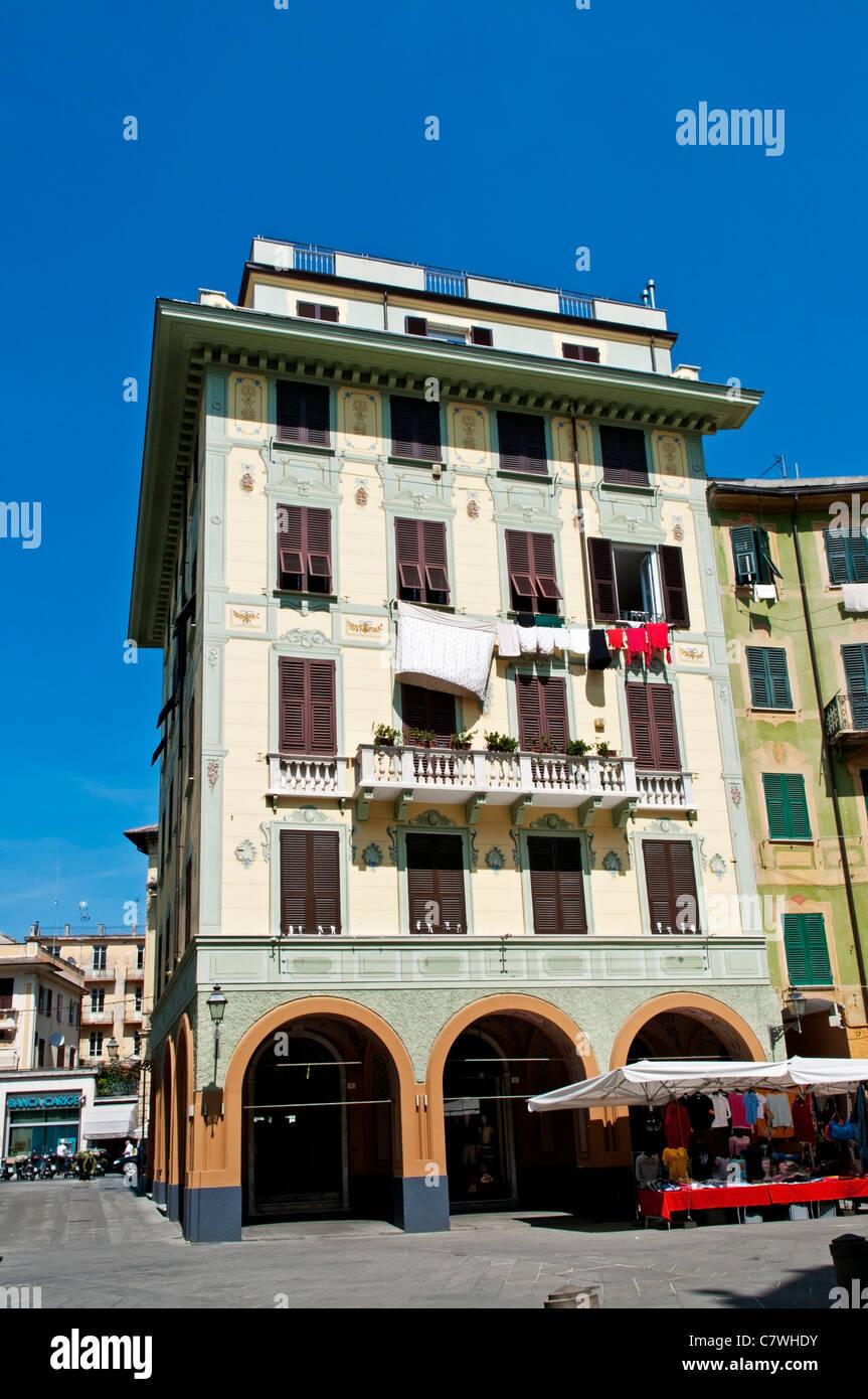 Un bloque de apartamentos pintado en colores pastel por encima de una fila de tiendas en la plaza sombreada de Caprera, Santa Margherita Ligure, Italia Foto de stock