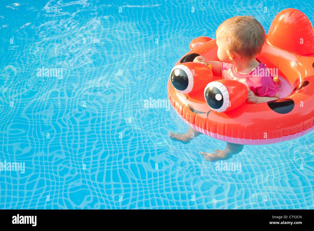 Niño pequeño dispositivo de flotación mirando a otro lado mientras flota en una piscina solo Imagen De Stock