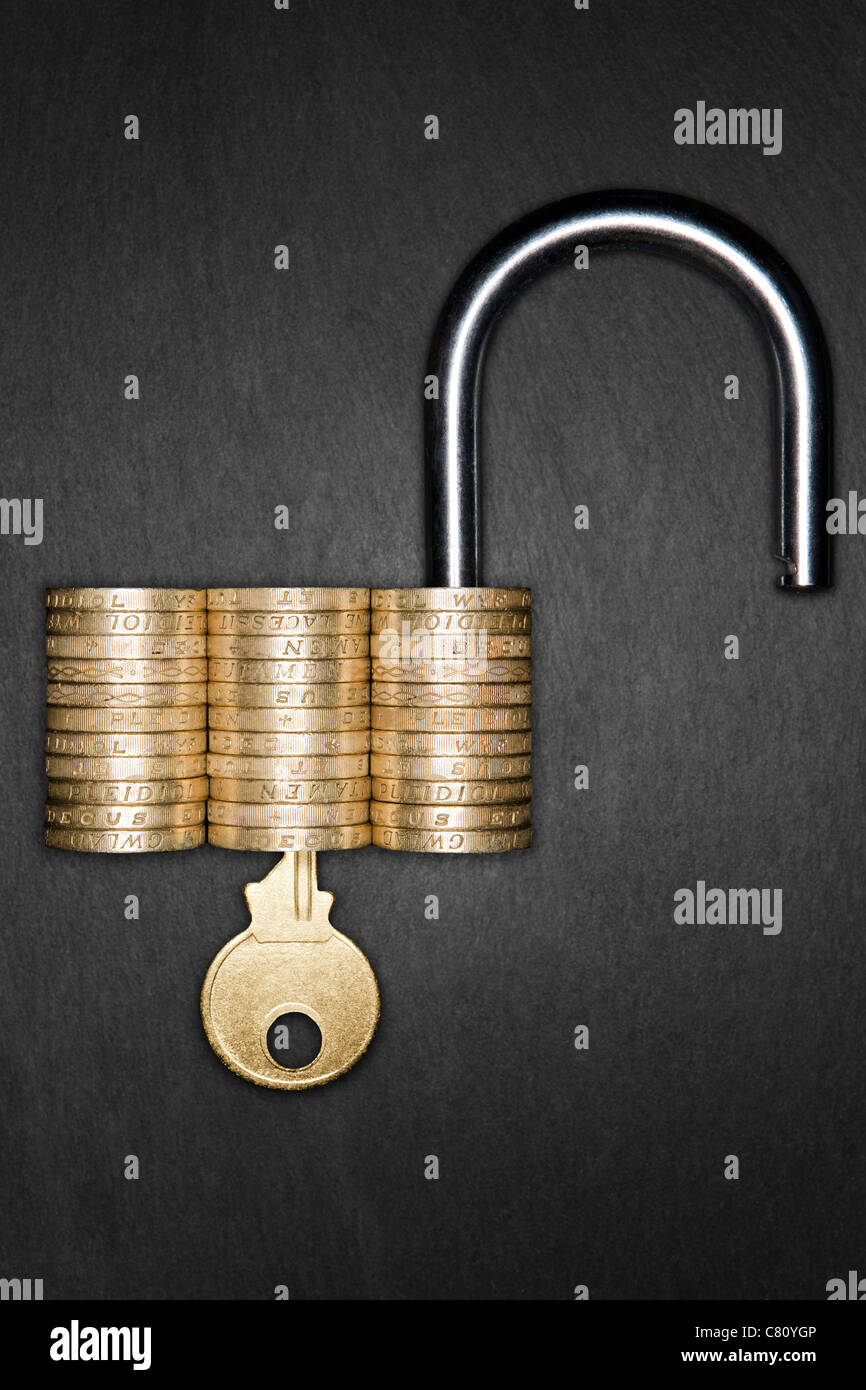 Concepto de seguridad financiera. Candado desbloqueado hecho de monedas de libra con una llave de oro insertada Foto de stock