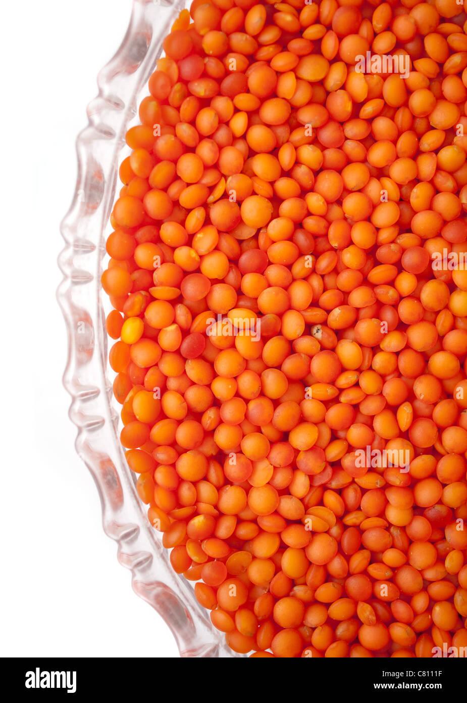 Lentejas rojas en una placa de vidrio, aislado sobre fondo blanco. Imagen De Stock