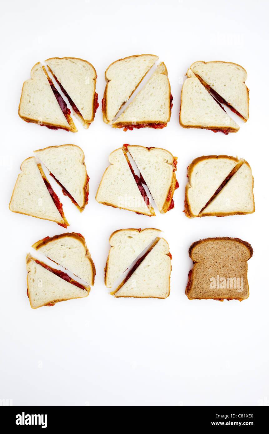 Sándwiches de mantequilla de maní y mermelada, uno en el pan de trigo entero Foto de stock