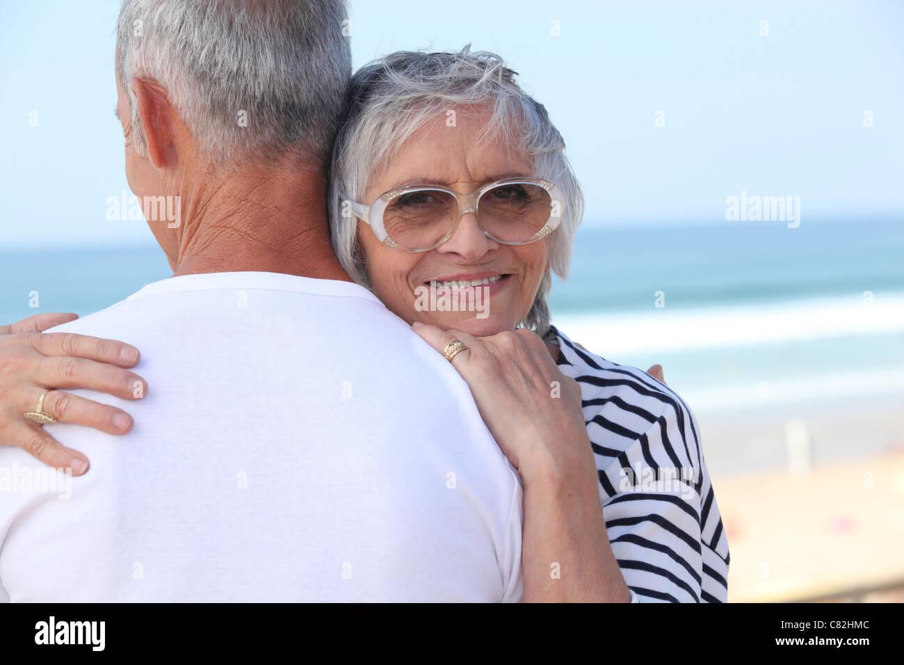 Pareja de ancianos abrazarse por una playa Foto de stock