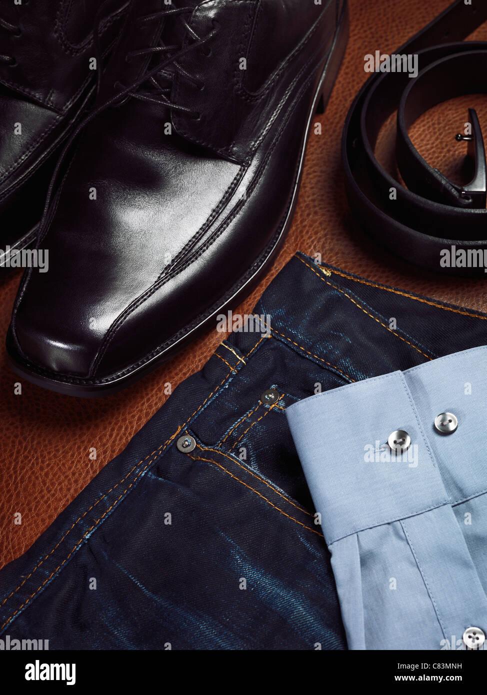 Mens fashion still life. Primer plano artístico de zapatos de vestir, jeans, una correa y una camiseta. Imagen De Stock