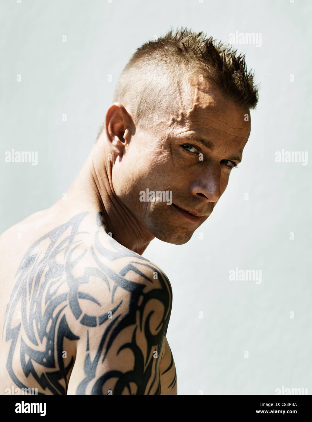 Hombre con tatuajes tribales para llevar al hombro. Imagen De Stock