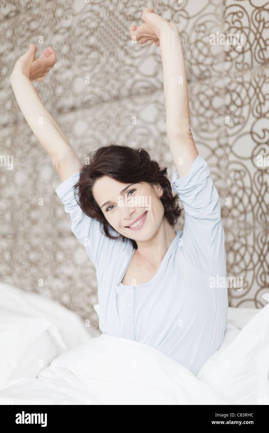 Mujer sonriente estiramiento en la cama Imagen De Stock