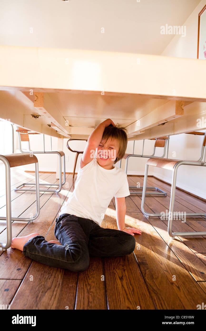 Muchacho sentado debajo de la mesa de comedor Imagen De Stock