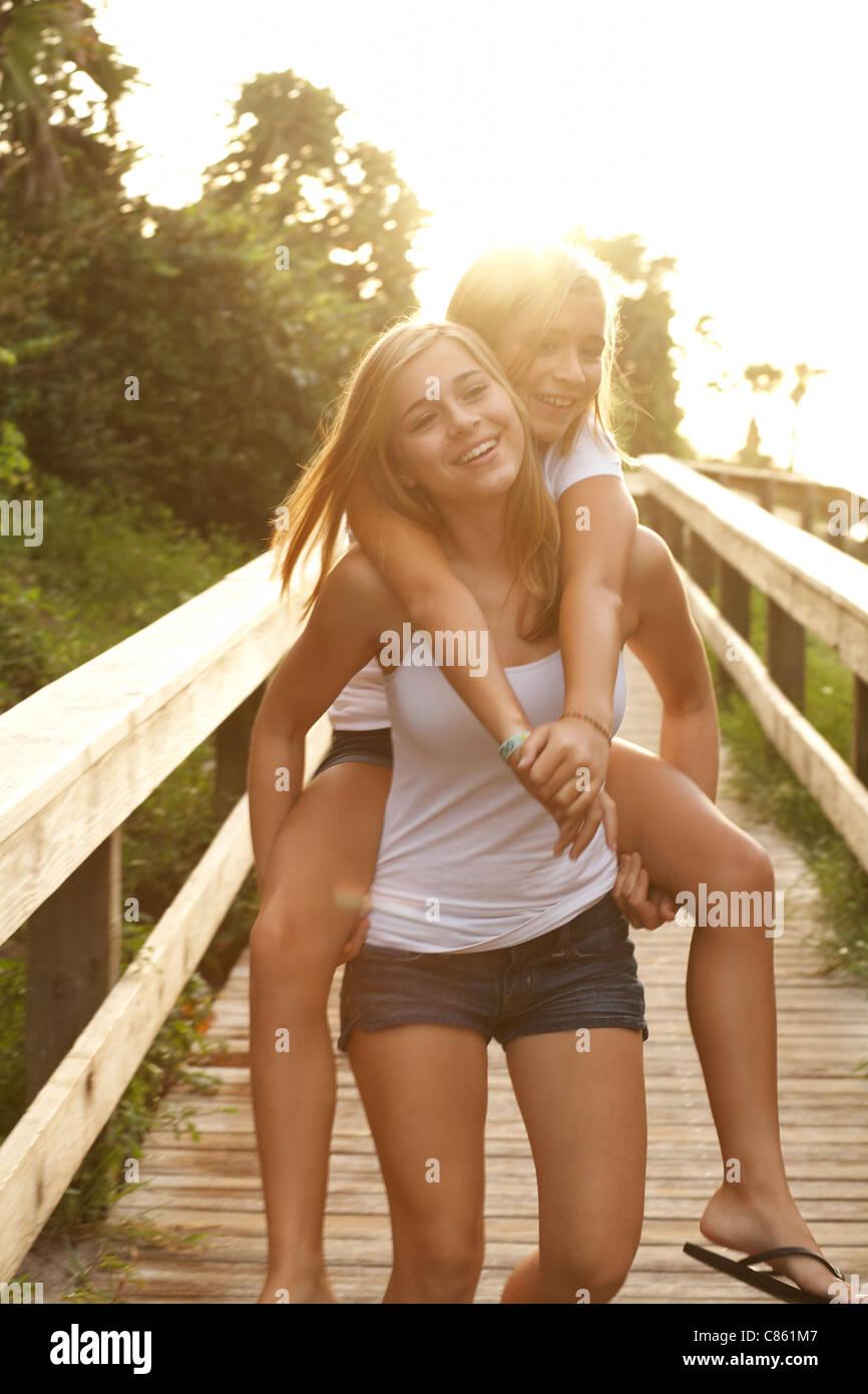 Hermanas jugar piggy back en el beach boardwalk Imagen De Stock