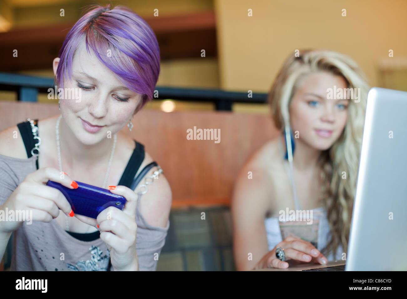 Dos chicas adolescentes en coffee house en portátiles y teléfonos inteligentes. Imagen De Stock