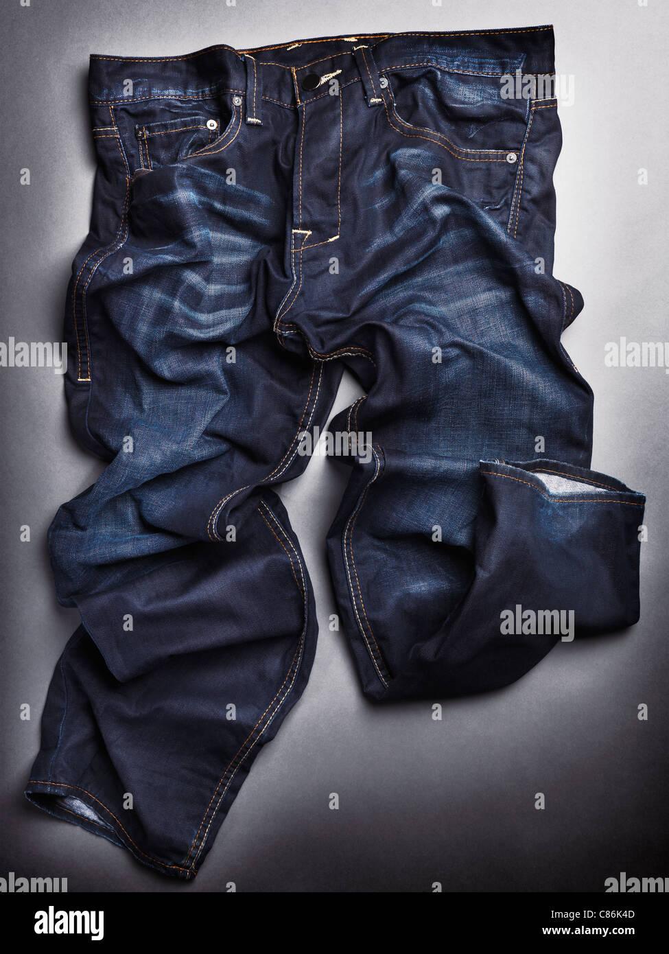 Foto de artísticamente lavados a la piedra azul arrugado mens jeans sobre fondo gris Imagen De Stock