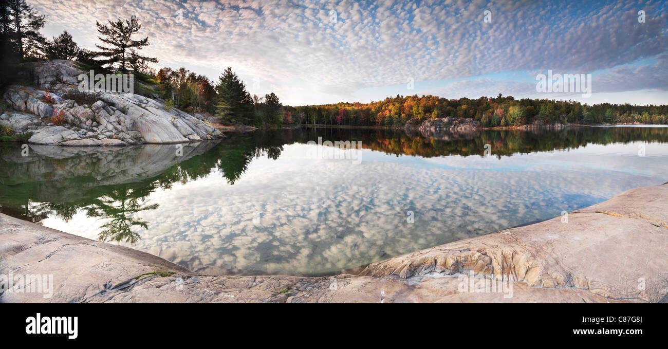 Rocas y árboles de otoño en una orilla del lago George. Hermoso paisaje panorámico de la naturaleza caída. Killarney Provincial Park, Ontario Foto de stock