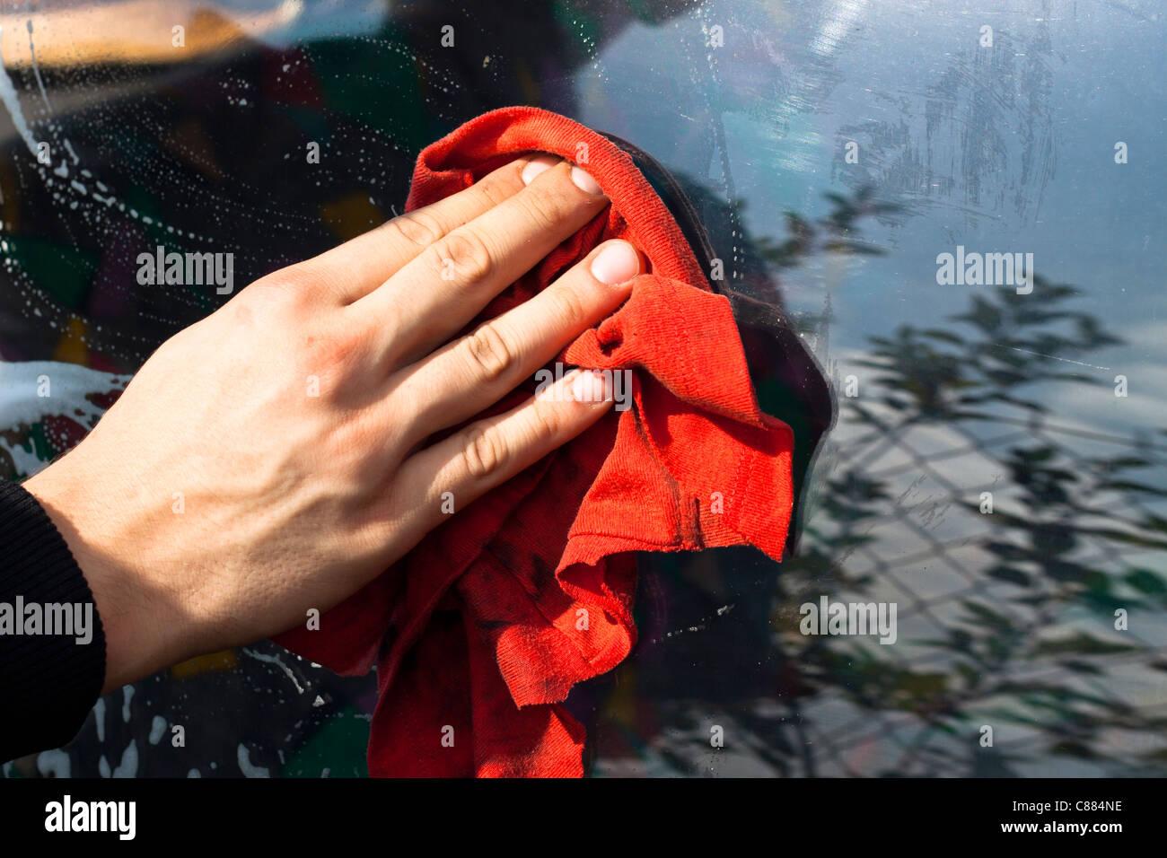 La mano del hombre con trapo rojo lavado car window. Imagen De Stock