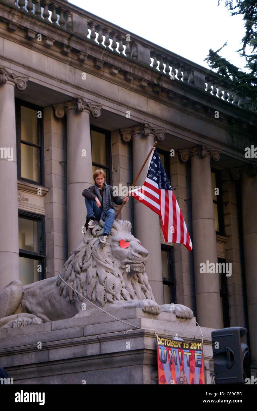 Manifestante sosteniendo una bandera americana al ocupar Vancouver rally delante de la Galería de Arte de Vancouver, Imagen De Stock