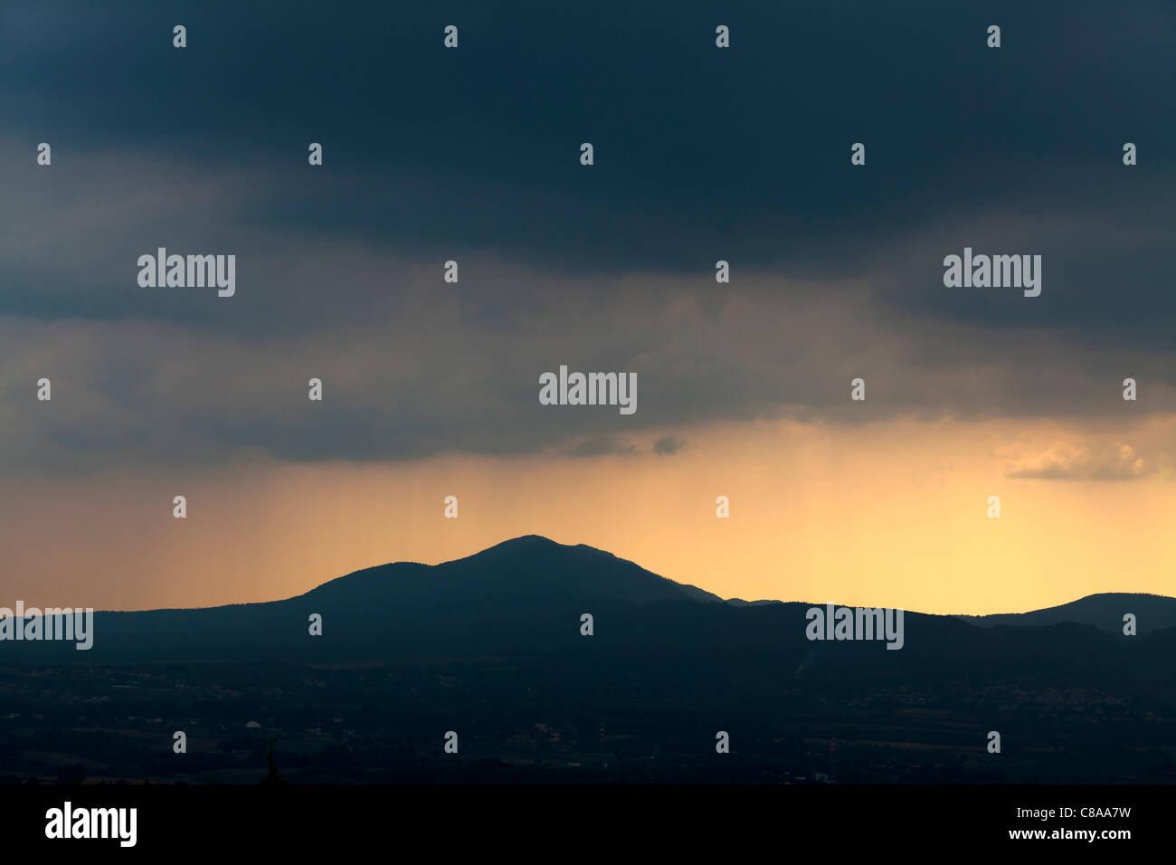 Nublado cielo oscuro con resplandor amarillo más allá de colinas Imagen De Stock
