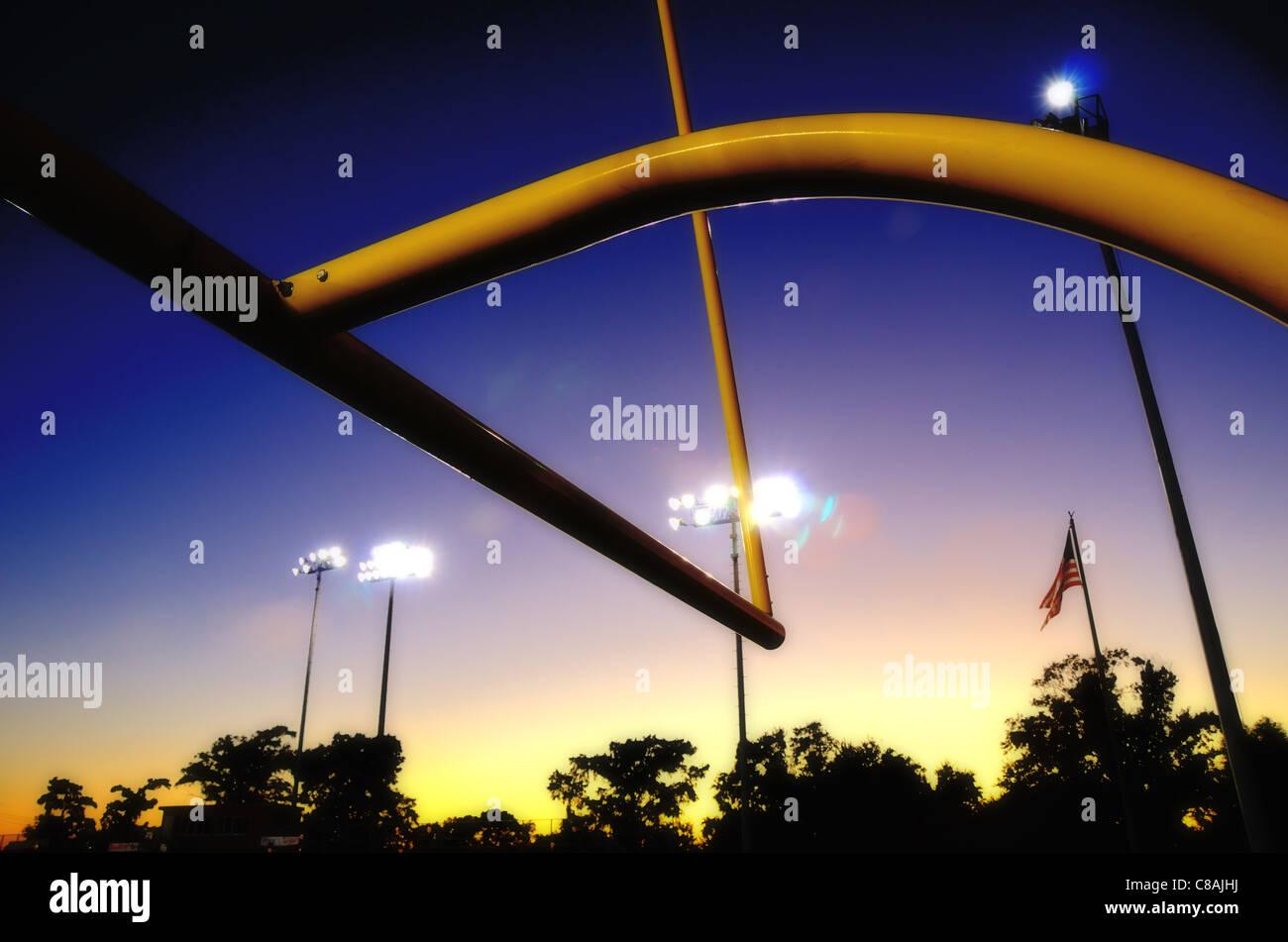 Fútbol americano goalpost al atardecer, con siluetas de línea de árboles y la bandera estadounidense Imagen De Stock
