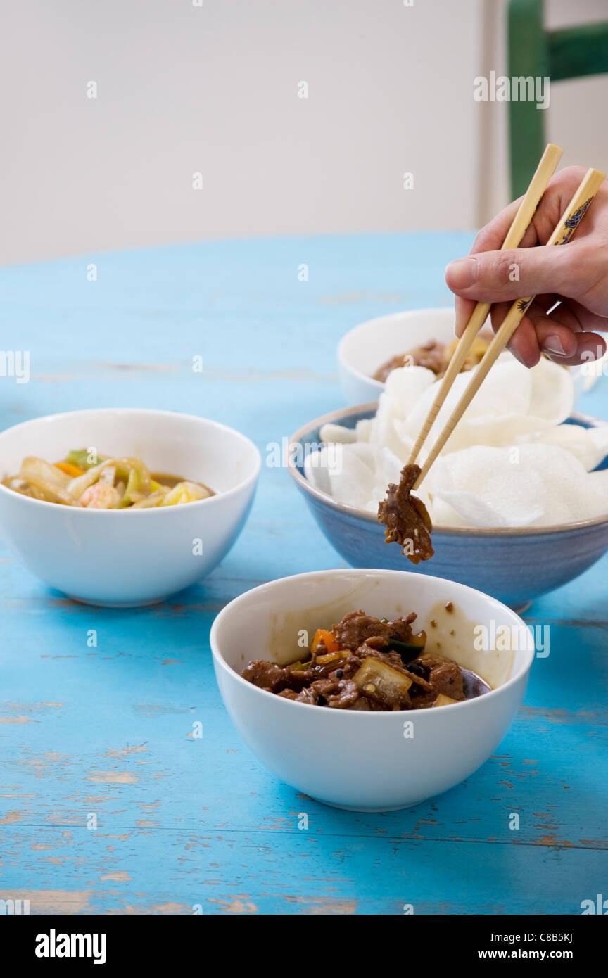 Cierre de la mano humana con palillos, la celebración de los alimentos Imagen De Stock