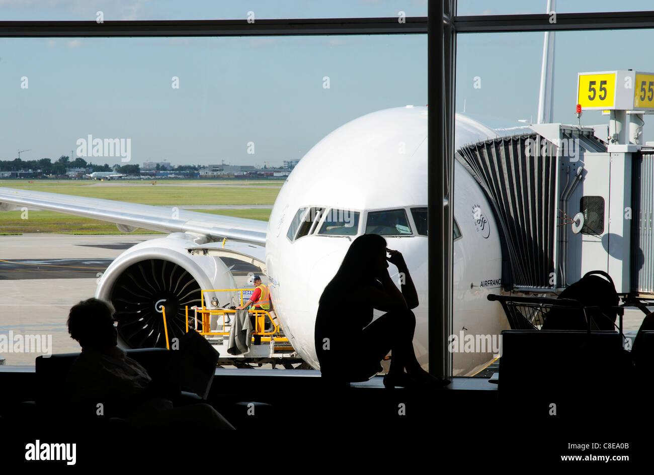 Una mujer joven en un teléfono móvil en silueta en un aeropuerto con un plano detrás de la ventana Imagen De Stock