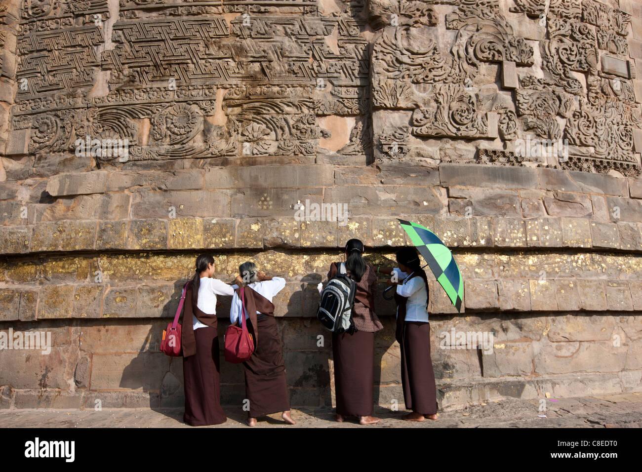 Los visitantes budista aplicando hojas de oro como oferta tradicional en ruinas Dhamakh Stupa en Sarnath, cerca Foto de stock