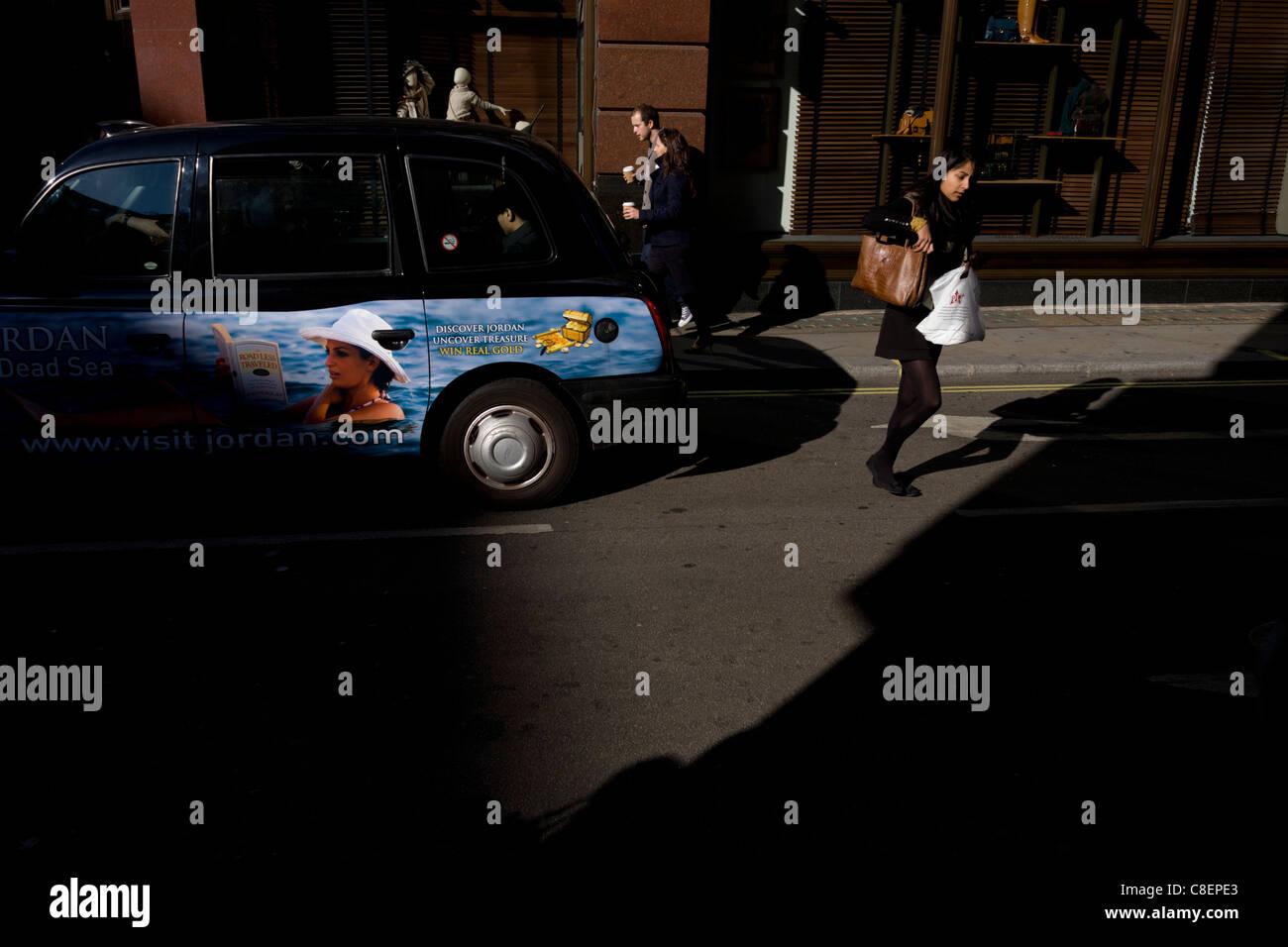 Un anuncio de vacaciones de Jordania en el lateral de un taxi de Londres y una concurrida carrera mujer que cruza Foto de stock