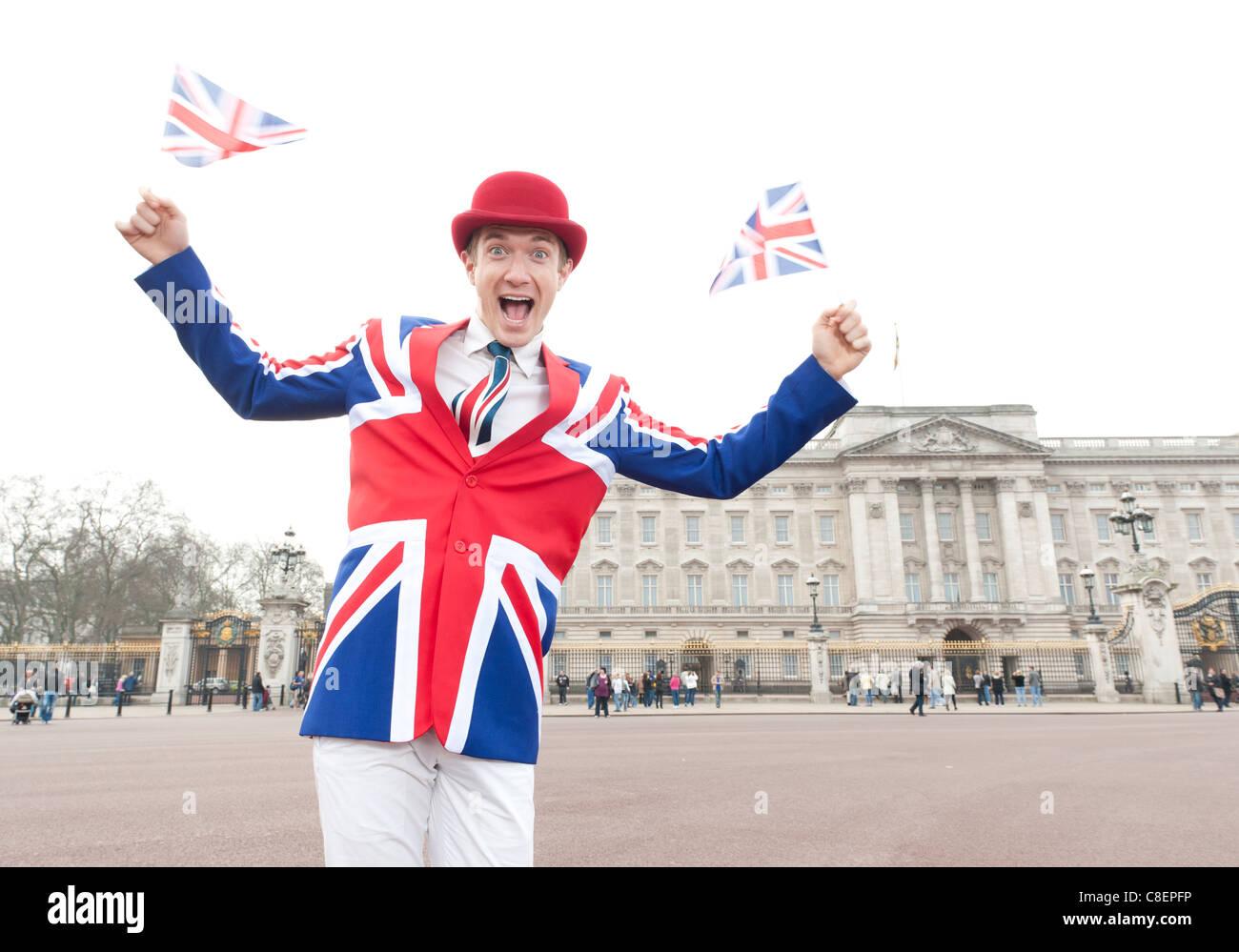 Patriótica Union Jack hombre vestido con traje ondeando banderas sindicales en el Palacio de Buckingham, en Imagen De Stock