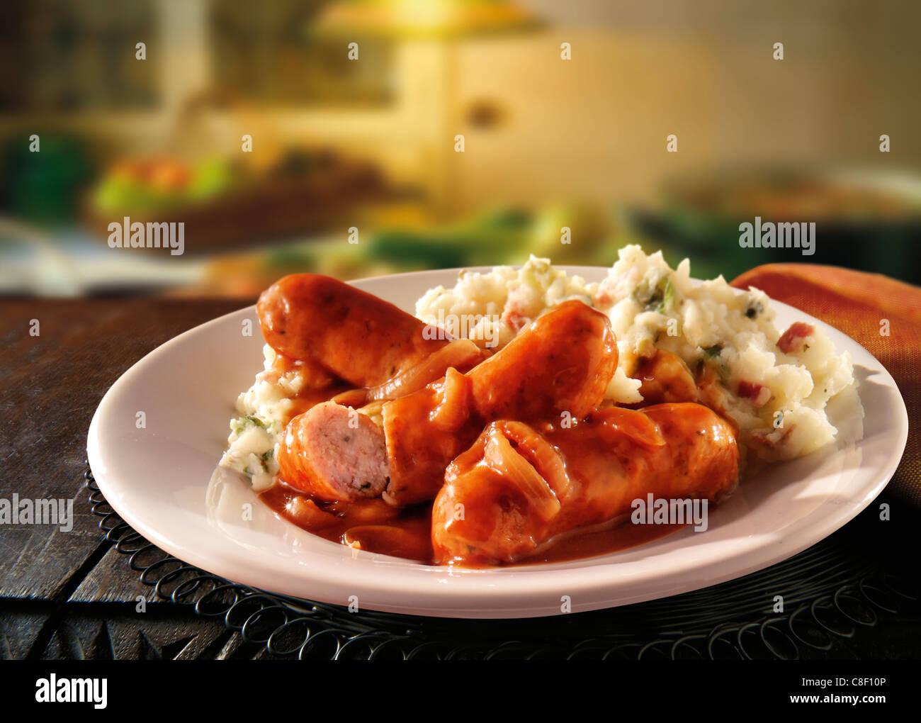 Cocinado tradicional salchichas y puré de patatas servido en un plato blanco en una mesa dispuesta para comer Foto de stock