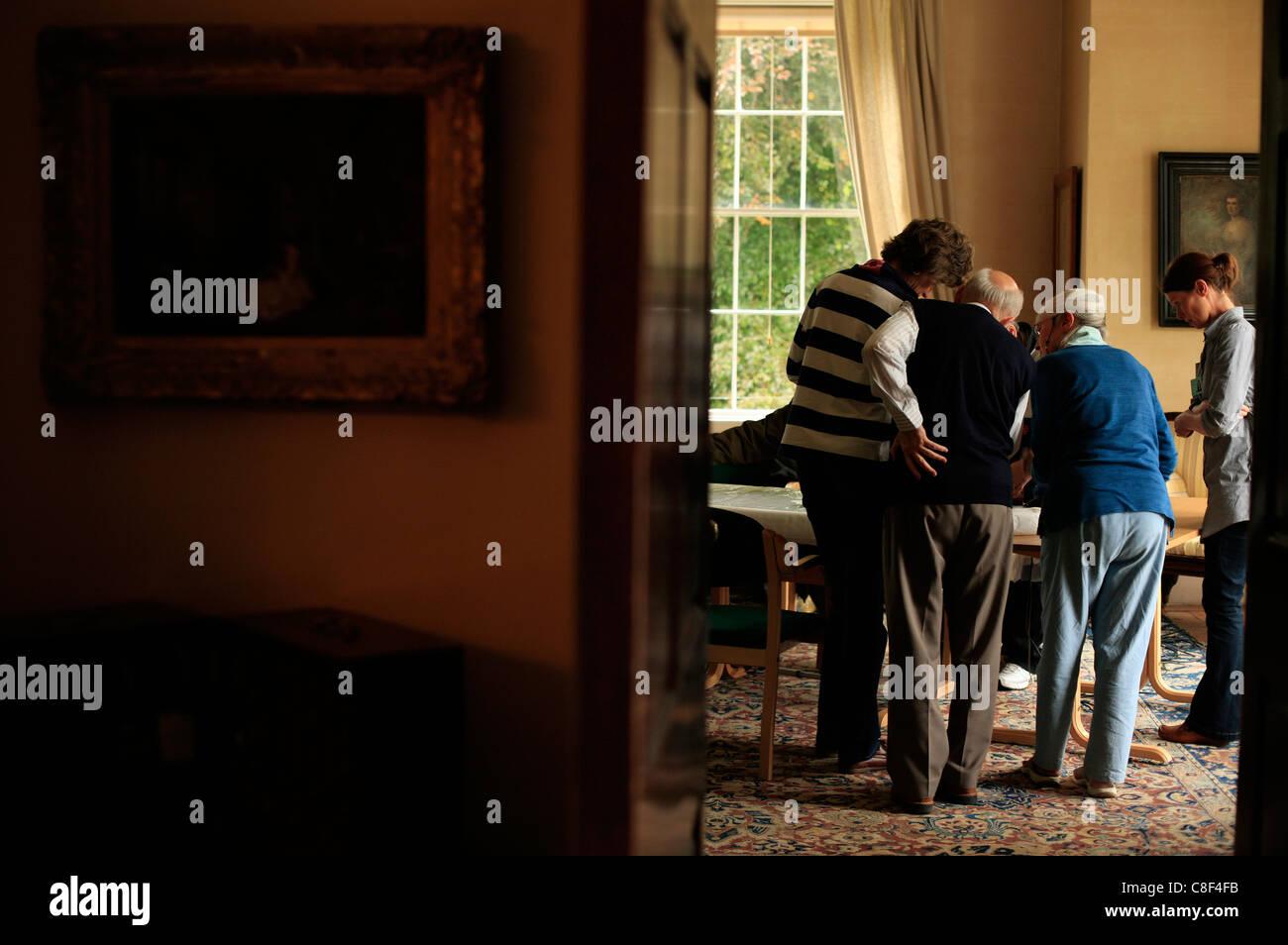Los ancianos se reúnen para ver libros dentro de una casa histórica Imagen De Stock