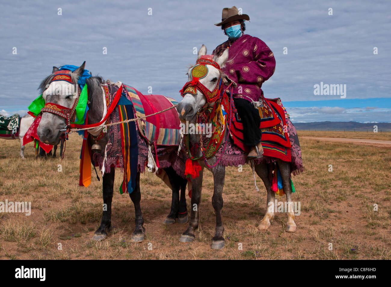Jinete en caballo colorfuly vestida en la estepa del oeste de Tíbet, China Imagen De Stock