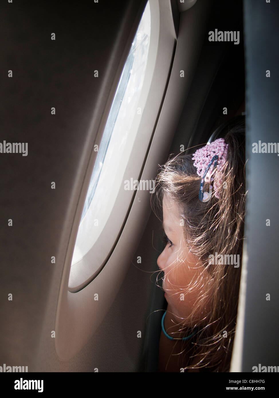 Niño mirando por la ventana en un avión Foto de stock