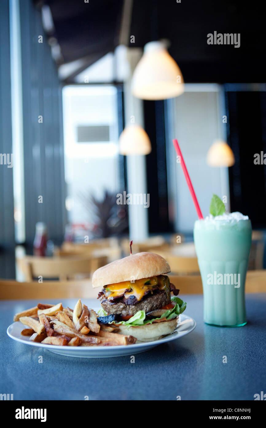 Hamburguesa con queso, papas fritas y malteadas en diner Foto de stock