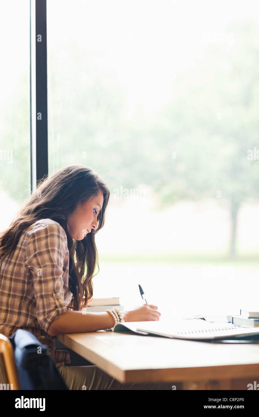 Retrato de un joven estudiante serio escribir un ensayo Imagen De Stock