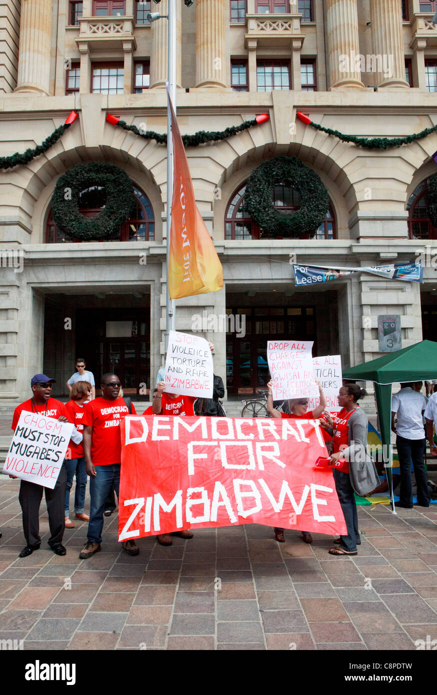 """Mugabe contra los manifestantes sosteniendo un 'Democracia para Zimbabwe"""" banner en CHOGM 2011 protestas Imagen De Stock"""