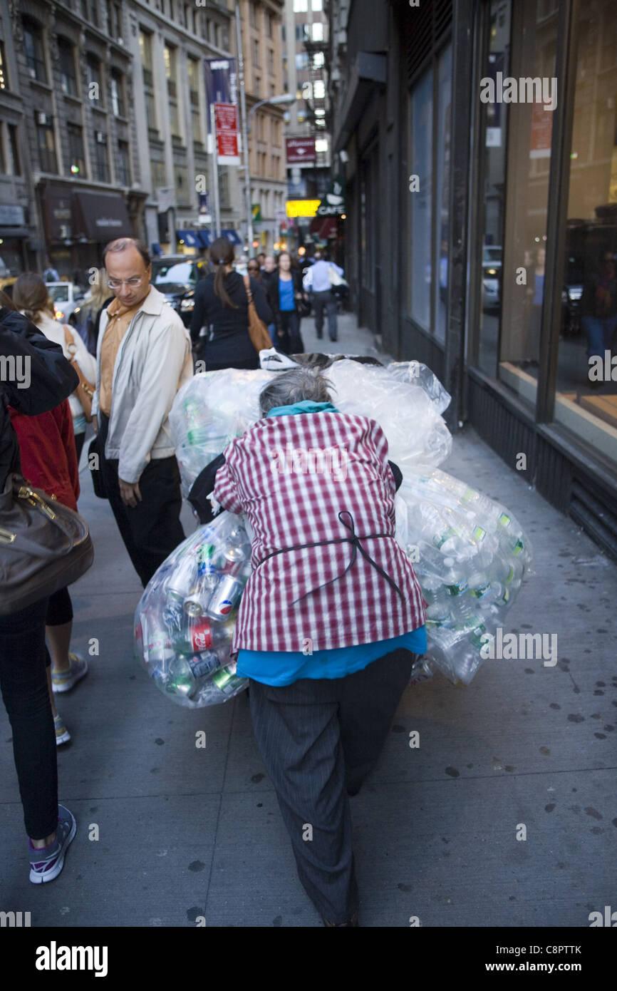 Mujer de edad recogiendo latas de aluminio en la calle en el distrito financiero de Nueva York refleja la economía Imagen De Stock