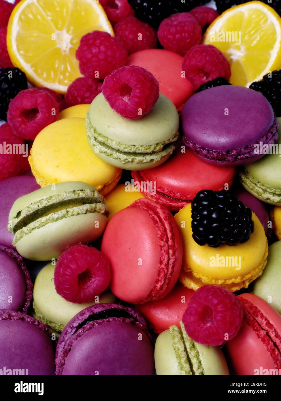 Limón, melocotón, fresa, grosella, pistacho, albaricoque y macarrones con rodajas de limón, frambuesas Imagen De Stock