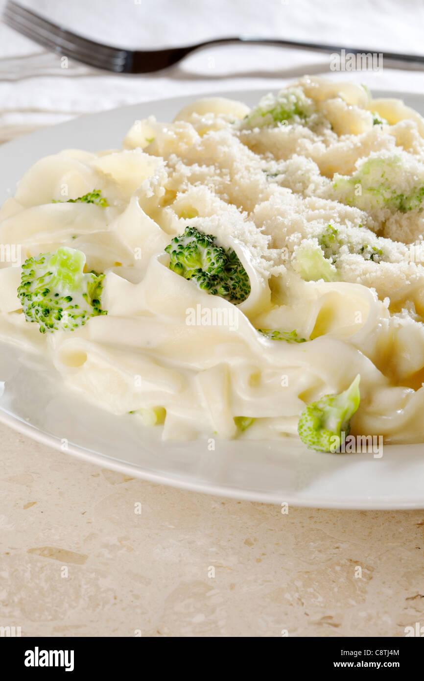 Tagliatelle pasta y brócoli en salsa cremosa con queso parmesano. Imagen De Stock