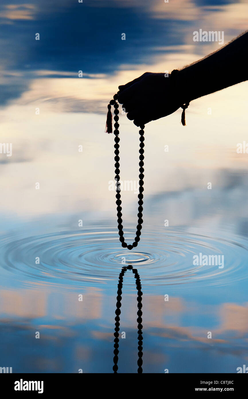 Mano sujetando Rudraksha indio / Japa Mala rosario más murmullo de agua . Silueta Imagen De Stock