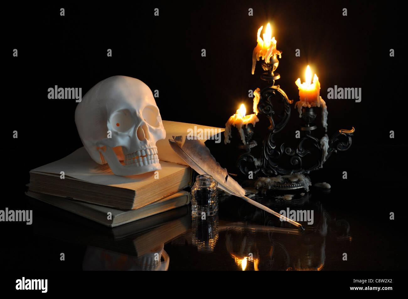 Bodegón con cráneo, libros y velas sobre fondo negro Foto de stock