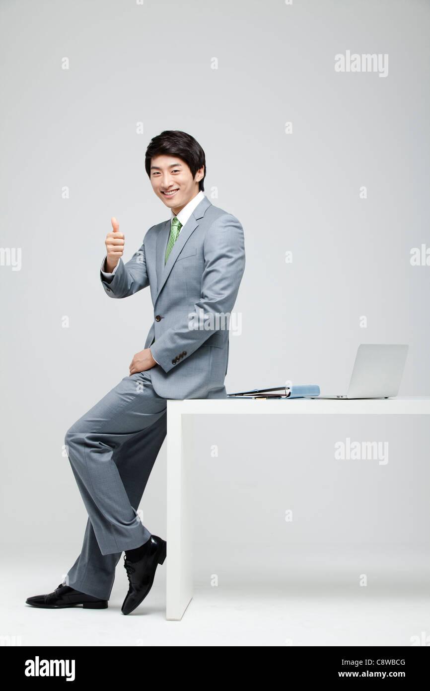 Retrato del empresario mostrando Pulgar arriba Firmar, portátil y el archivo en el escritorio Imagen De Stock