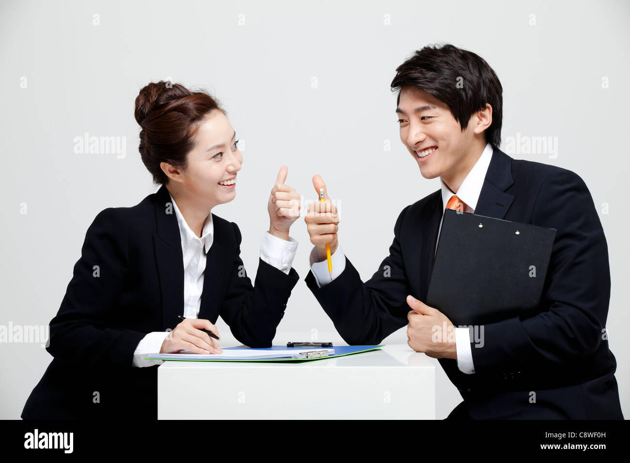 Empresario asiático y empresaria mostrando Pulgar arriba firmar en el escritorio, uno frente a otro Imagen De Stock