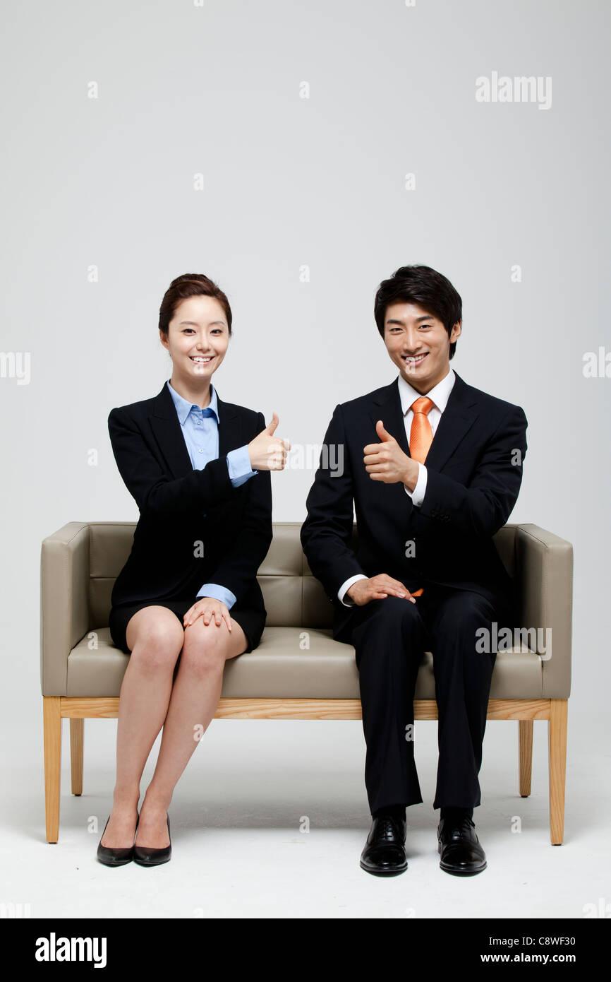 Empresario asiático y empresaria mostrando Pulgar arriba firmar y sentados en el sofá Imagen De Stock