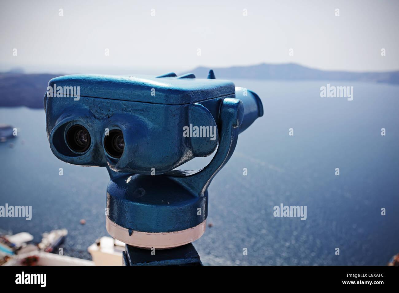 Binocular con monedas contra el Puerto de Fira, la isla de Santorini, Grecia. Imagen De Stock