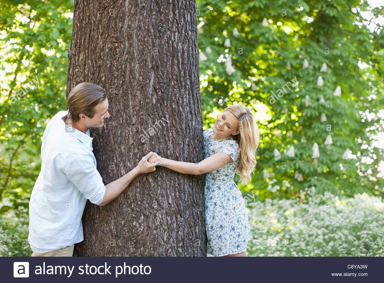 Las manos de la pareja alrededor del árbol Foto de stock