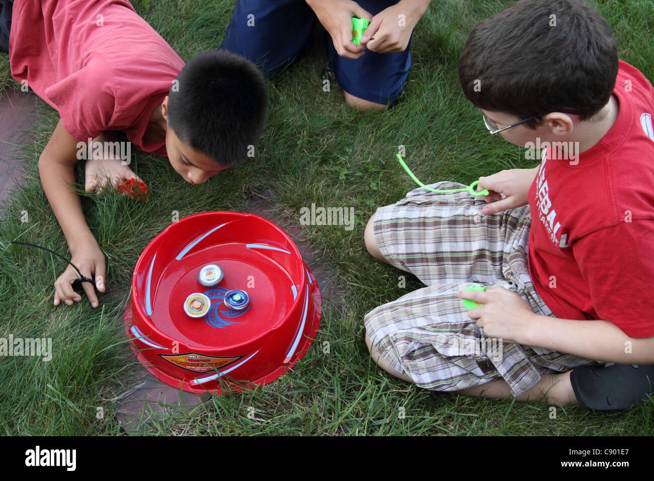 Bey Blade diversión 9-10 tres muchachos jugando en el estadio viendo Imagen De Stock