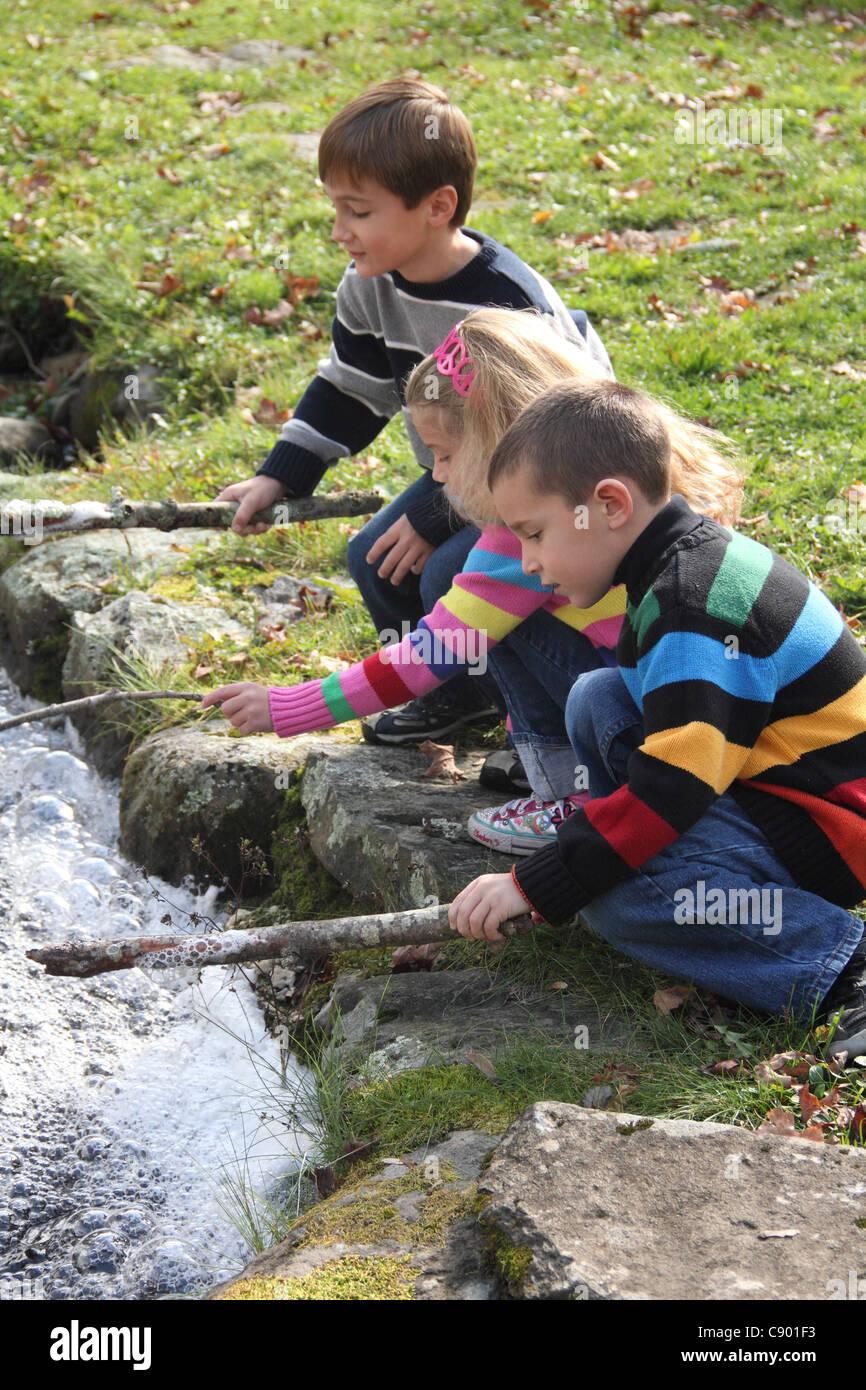 Tres Kid Amigos Jugando Con Palos En Parques Brook Metiendo Burbujas