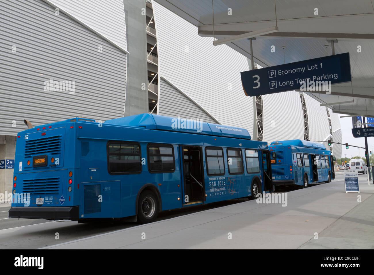 Los autobuses azules esperando en el bordillo de la acera para ir a la zona de aparcamiento de larga duración Imagen De Stock
