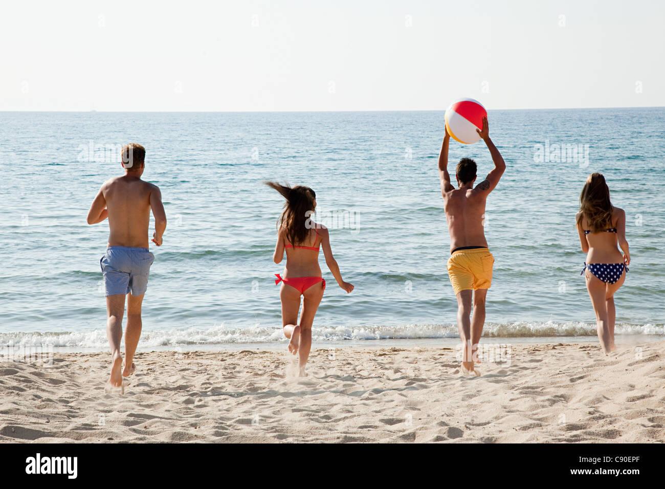 Cuatro personas jugando con la pelota de playa en la playa Foto de stock